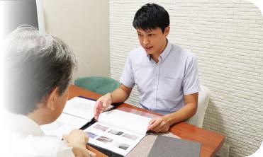 内装材の見本帳を手に賃貸マンションオーナー様と打ち合わせを行う吉川 聡一郎