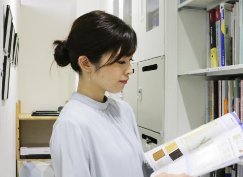 社内で営業と打ち合わせを行う東 悦子