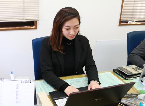 手帳とEメールでスケジュールのチェックを行う鈴木祐美子