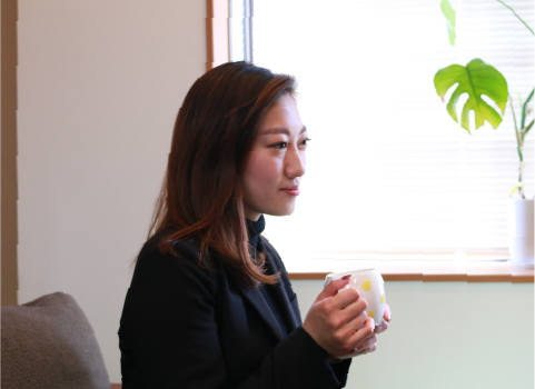 昼休みにマグカップでコーヒーを飲む鈴木祐美子
