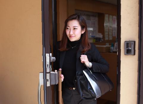 歩いて事務所を出る鈴木祐美子