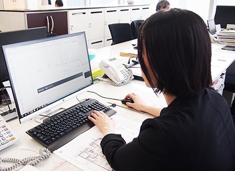 PC前で微笑む柴田 麻里